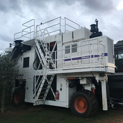 Olive harvester machine moving through the olive grove